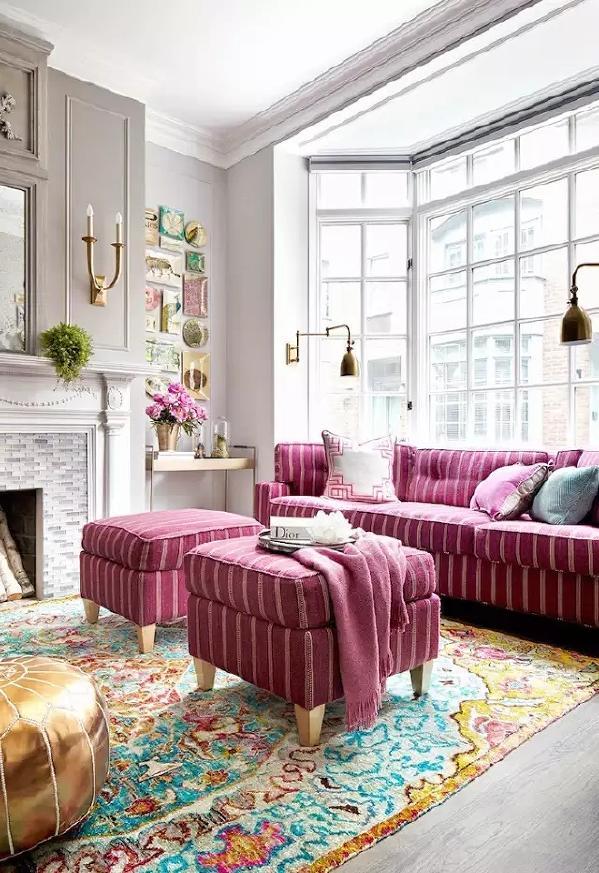 色彩艳丽的地毯搭配桃红色的沙发与金色懒人沙发,色彩的碰撞让客厅看上去很美  。