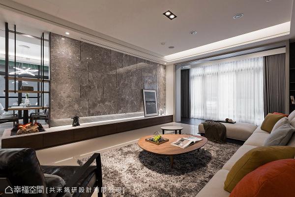 电视主墙以大面积石材拼贴呈现,形塑非凡大器质感,左侧搭配开放展示吊架与壁炉意象,为场域增添层次感与温暖意象。