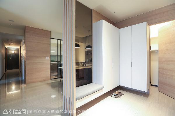 入口设置穿鞋椅和鞋柜,以梧桐木皮点缀墙面,让储藏室门片化于无形;结合格栅造型和茶玻带来通透设计,营造若隐若现的视觉效果。