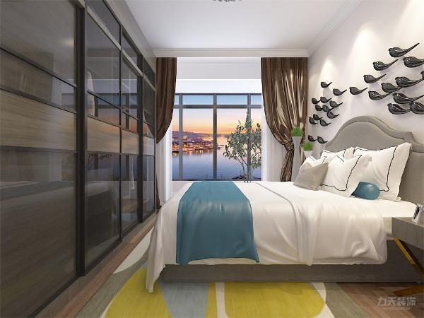 主卧墙面为奶卡色乳胶漆,简约的双人床与木色床头柜,再搭配上具有储物功能的浅木色色衣柜,整体空间简洁明亮极具现代感,蓝色点缀空间