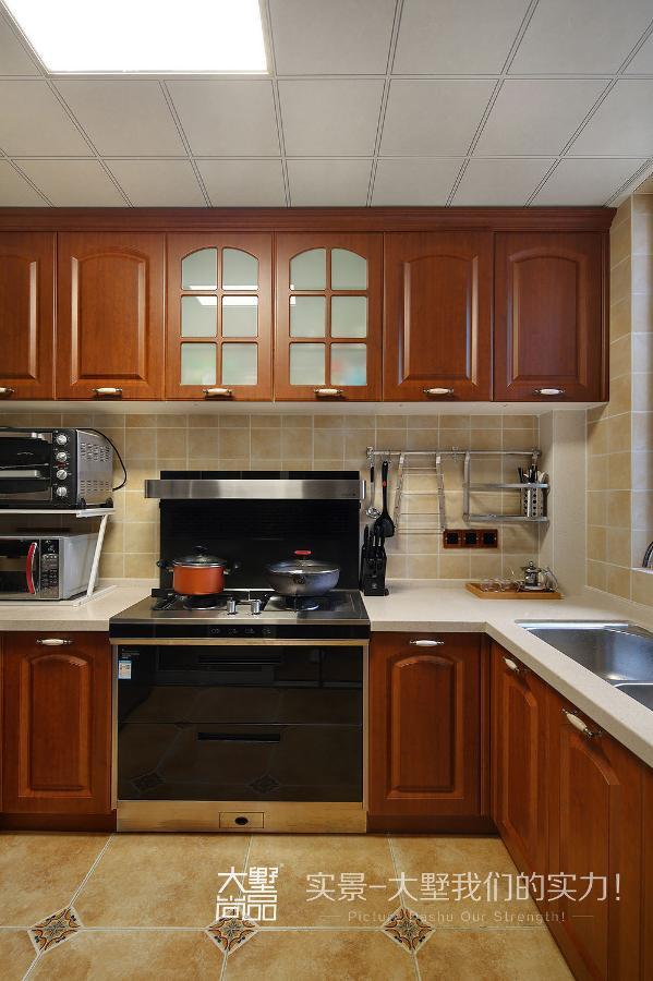 厨房的整体色调选择深色的橱柜,整个空间大气而实用。