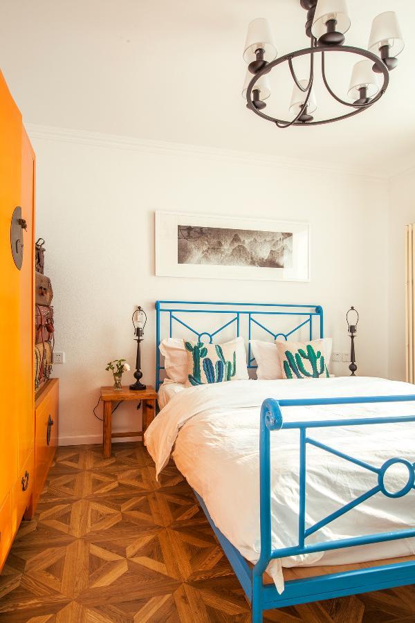 铁艺床曾陪了老曹十多年,是他请朋友用铁打的, 最初是铁的原色,后来被他们俩给刷成了蓝色。 墙上那幅画是老曹的摄影作品,为房间增色不少。