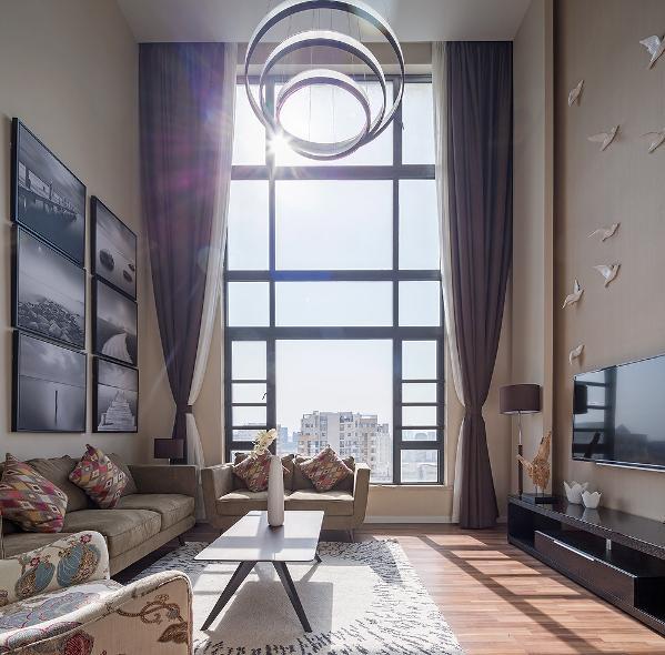 客厅整体暖色调,整体简约大气但绝不简单,良好的光照使整个客厅看起来温馨明亮。没有过多的装饰品,墙上的六幅装饰画与电视背景墙的飞鸟呼应,圆形吊灯将整个客厅点缀恰到好处。