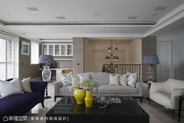 起居室一角增设精致阅读区,与梯间天井悬挂的巨形吊灯相映成趣。