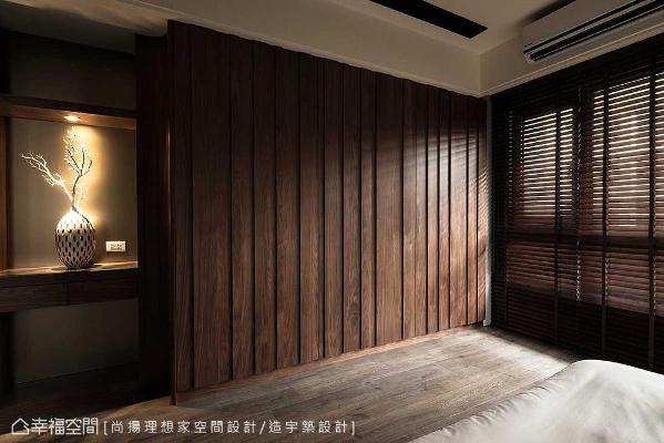 主卧房床尾的设计,左侧平台兼有迷你吧台的机能,右侧则设置整面式的衣柜,以层次交错的深色胡桃木表现。