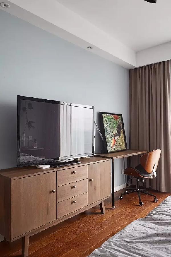 桃木色的电视柜一旁摆了一张小书桌,整体显得格外的舒适惬意;