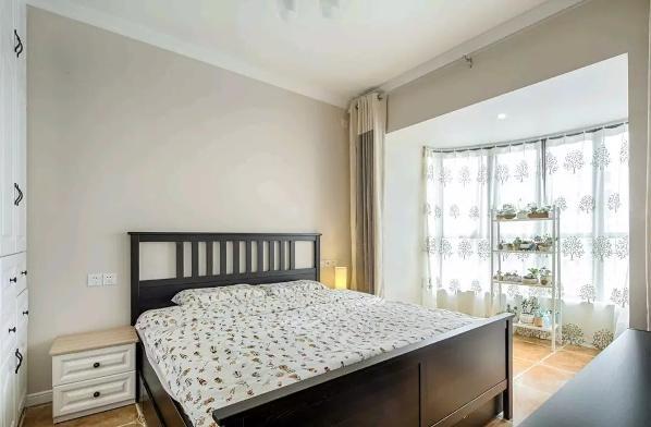 主卧把阳台打通,半圆形的阳台,为卧室带来了充足的光线,摆着植物架,更是让卧室显得清新舒适;
