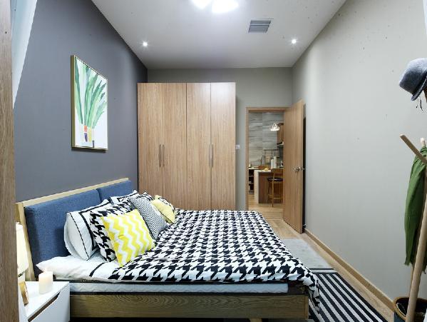 从阳台方向看主卧,进门靠墙的位置做了一组原木色定制衣柜