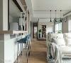 厨房以半开放式手法呈现,并延伸出休闲吧台,搭佐蓝绿色高脚椅,点缀场域色彩层次。