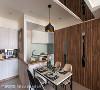 玄关收纳柜的台面与餐厨空间的吧台齐平,并利用同色系腰饰串连,形成视觉延伸效果。