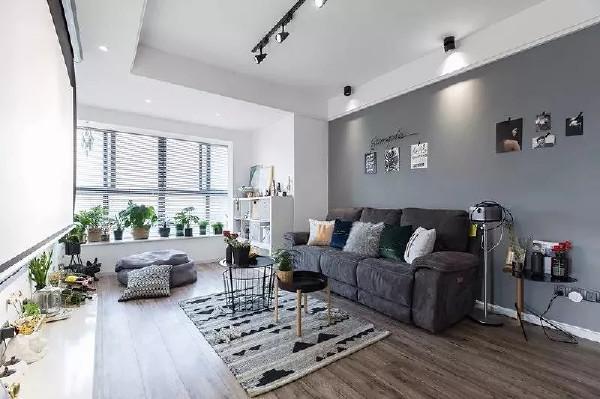 深色的沙发舒适且柔软,阳台的纳入拓宽了客厅的空间。