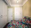 次卧墙体以淡淡的茶绿色,白色的房门与衣柜,搭配一款鲜艳花纹的床单,还有一盏星状的吊灯,这个空间简简单单而又实用优雅自然。