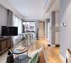 客厅的整个色调分为三个部分,一是墙面的浅灰色,低调中又带点清新,二是吊灯的纯白色,干净大气,三是地板上的木色,三个颜色形成三个大色块,地板砖的拼接方式拉伸了客厅的纵深感。