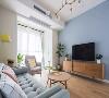 在餐厅的另一侧就是客厅空间,背景墙同样选择了以蓝色为主,搭配木质感的茶几、电视柜,清新而又自然。