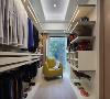 在主卧室的内部还有一个独立的衣帽间空间, 开放式的隔板架、柜子等组合起来,方便摆放不同的衣物,摆放一个亮黄色的单椅,亮眼又实用。