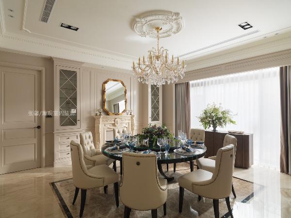 餐厅有着华丽的水晶吊灯,我们为屋主挑选黑色钢琴烤漆的餐桌,远看不起眼,然而近瞧质感倍增。餐椅就以简约、有小复古钉扣造型堆出华丽感,加上我们常用的壁炉,就是干净、古典形式,平衡整体的华丽度。
