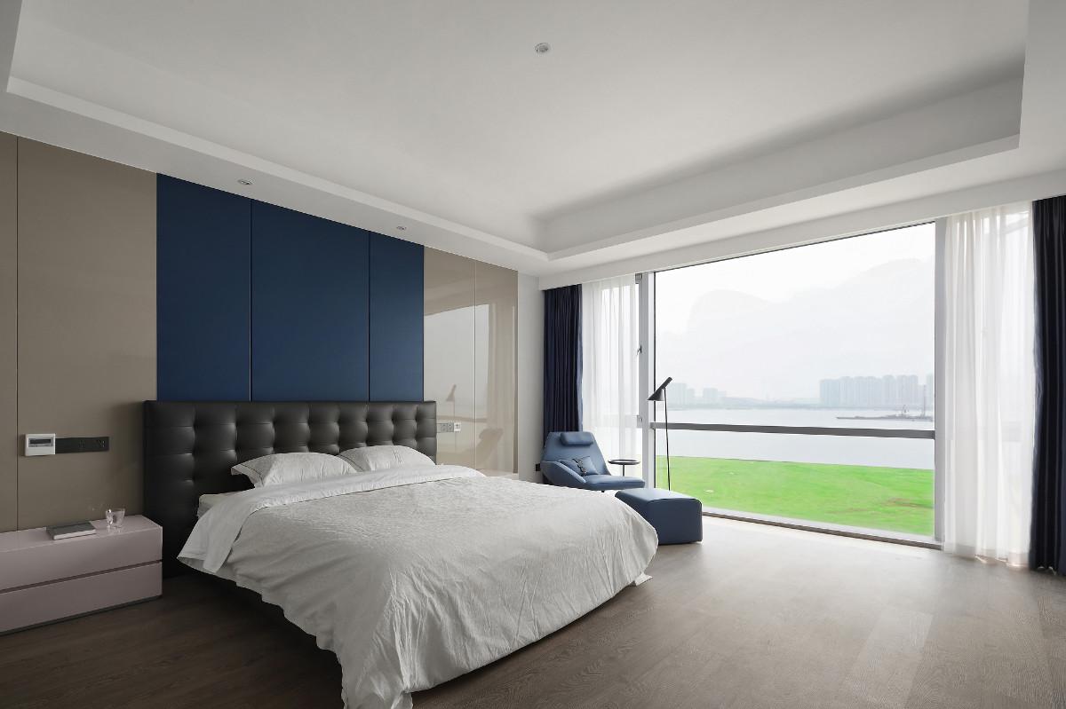 整面落地窗的设计使整体更加具有空间感,蓝色背景墙与蓝色沙发椅搭配空间,与窗外的湖景相互辉映。