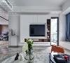 以白色为主色调,地面铺贴浅棕纹理进口大砖,延展温润气息,加之蓝色、红色作为点缀,使空间更显清新透亮。温和感极强的木色消解了整面白色电视柜带来的单调感,亦可作为绝佳的陈列台。