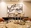 餐厅的设计效果,圆形大理石双层台面的餐桌,搭配几把舒适的棕色餐椅,行云流水般的水墨画,云彩图案的装饰,