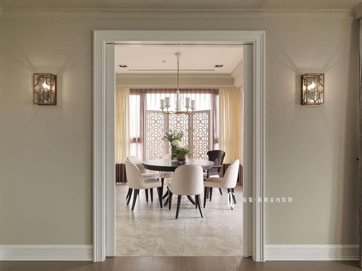 以玻璃拉门将客厅与餐厅相阻隔,拥有独立空间,利用白色收框线条及对称的小中式窗棂壁灯,框出一道生活景致。