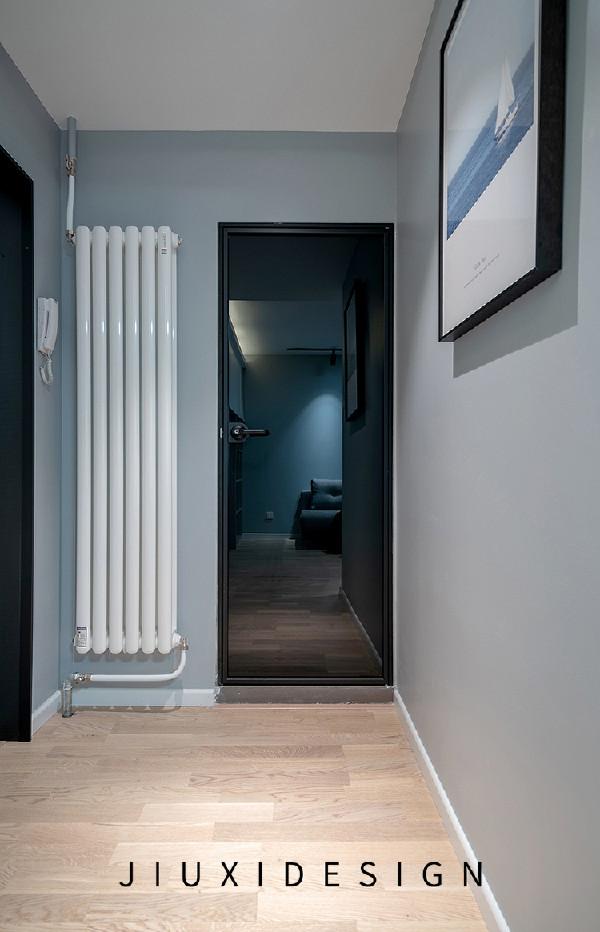 玄关左边是卫生间,选用了钛镁合金门,它的硬度高、抗磨性与抗腐蚀性强,搭配黑色玻璃能保证内部私密性。黑色镜还可以作为入户区域的穿衣镜来使用。