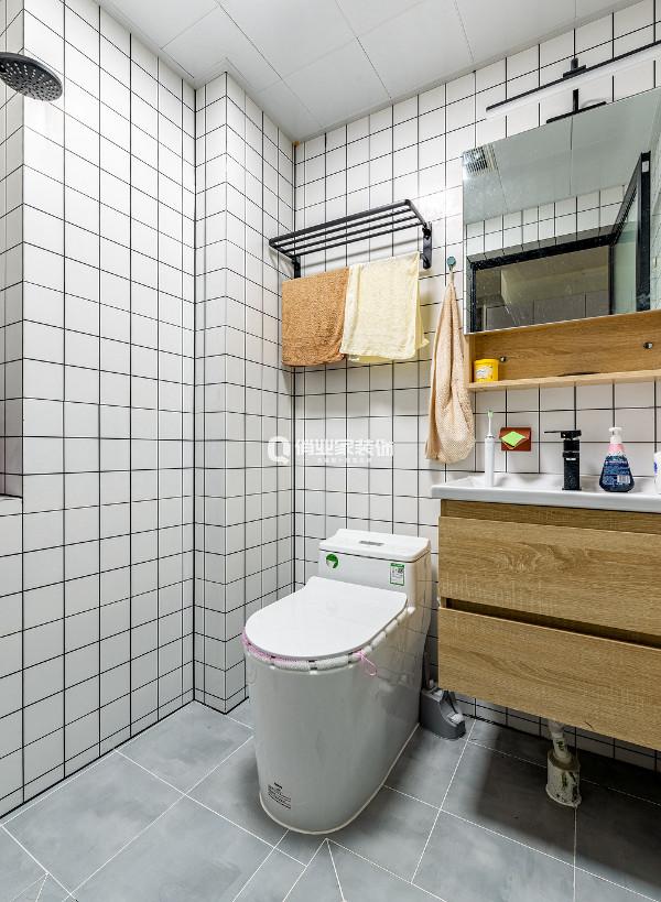 卫生间的墙面用小白砖装饰,搭配原木色的洗手盆柜,呈现出简约而不寡淡的设计品味。