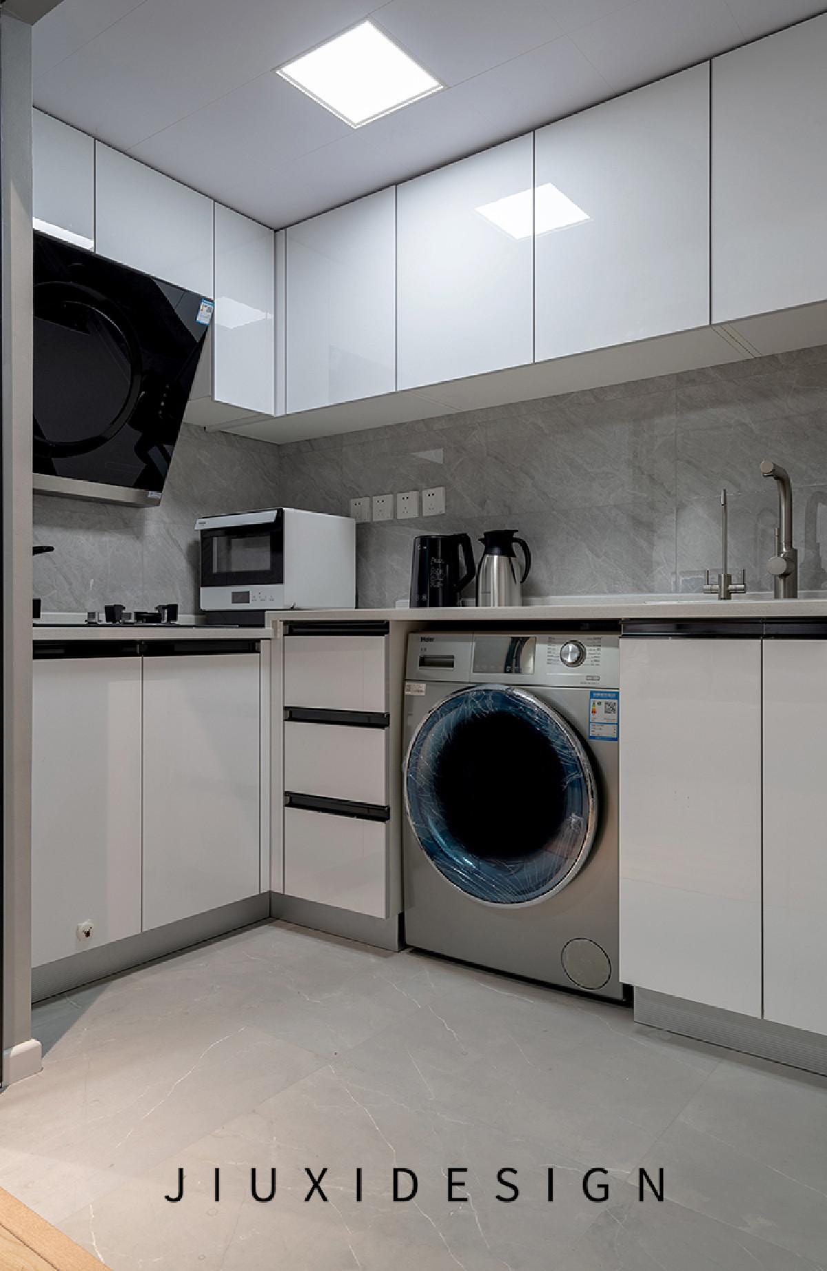 橱柜颜色选用了白色,因空间大小有限,灶台与油烟机的尺寸需要掌握非常精确才能够正常安装使用。洗衣机镶嵌在橱柜内,释放其他操作空间。