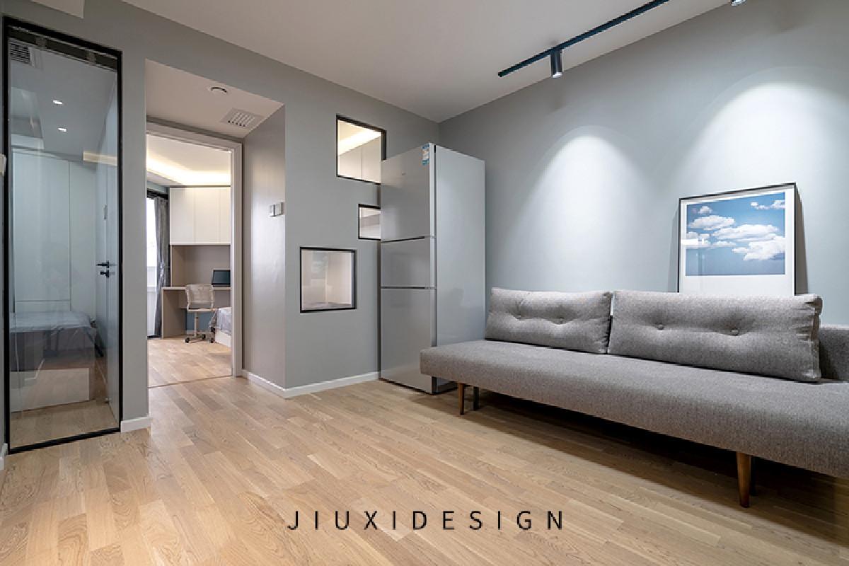 原木色的实木工字地板增加了客厅的纵深感,浅灰色的墙面给空间增添了几分高级。